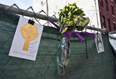 Flowers and cards are tied to the fence surrounding 218 Arch St as a memorial to the dead buried there.